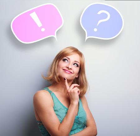 Penser jeune femme mignonne avec interrogation et d'exclamation signes dans des bulles au-dessus de la tête sur fond bleu Banque d'images