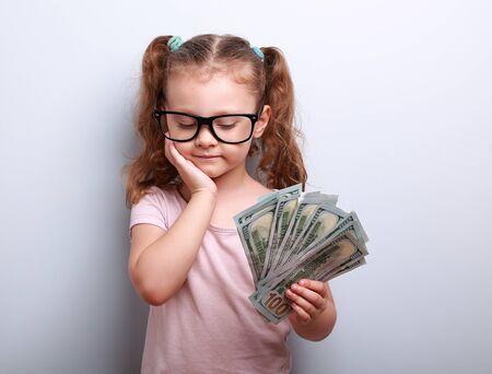 pensando: Chico lindo serio en vidrios que miran en d�lares en la mano y pensando c�mo gastar el dinero de la mano de la cara