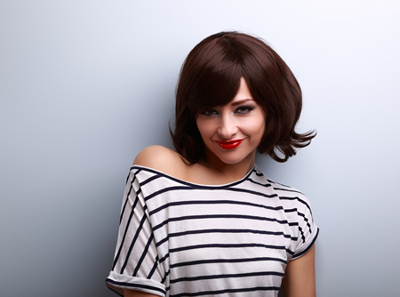 woman hairstyle: Flirting young woman with short hair style and red lipstick looking on blue background
