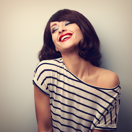 face close up: Fun laughing young woman with short hairstyle and closed eyes. Vintage portrait Stock Photo