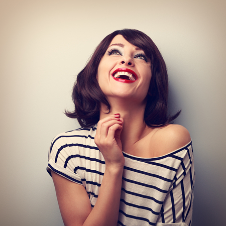 Happy loudly laughing young casual woman looking up. Vintage closeup portrait Stock Photo