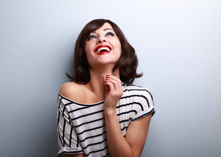 natural looking: Happy natural toothy laughing young woman looking up on blue background with empty copy space