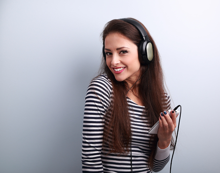 smile face: Happy toothy smiling teenager in headphones listening the music from player on blue background with empty copy space