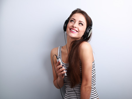 Pretty smiling girl listening the music wearing headphones holding in hand thre phone and looking up on blue background