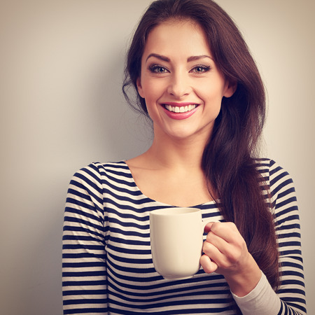 tea hot drink: Happy toothy smiling casual young woman with cup of tea. Vintage closeup portrait
