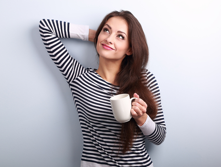Casual attractive thinking woman holding cup of tea and pensive looking up on blue background