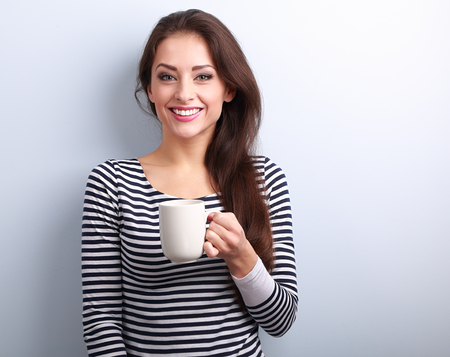 portrait young girl studio: Happy toothy smiling casual young woman with cup of tea on blue background with empty copy space