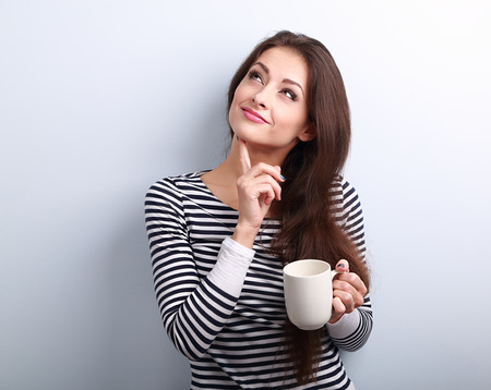 Thinking concerned young woman looking up with cup of coffee on blue background