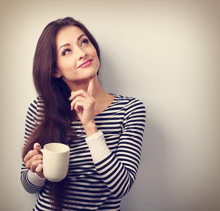 mujer pensando: Pensando en la mujer joven en cuestión mirando hacia arriba con la taza de café. Retrato de la vendimia