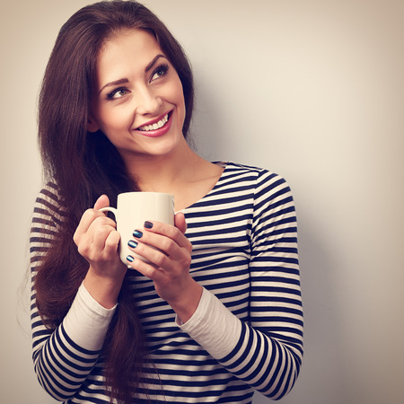 women holding cup: Beautiful calm thinking woman drinking hot coffee from cup. Vintage closeup portrait