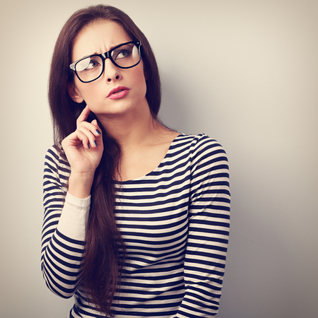 concerned: Annoyed angry young woman in eyeglasses thinking and looking up. Vintage closeup portrait Stock Photo