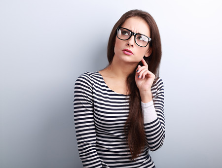 Molesto mujer joven enojado en lentes pensando y mirando hacia arriba sobre fondo azul Foto de archivo