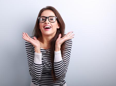 Verrassende opgewonden jonge vrouw met open mond gebaren handen op een blauwe achtergrond met lege kopie ruimte