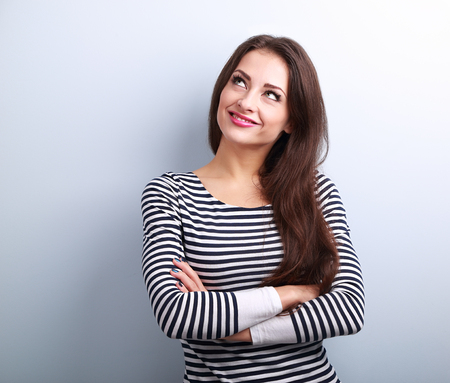 Happy thinking casual girl with folded hands looking up on blue background with empty copy space Archivio Fotografico
