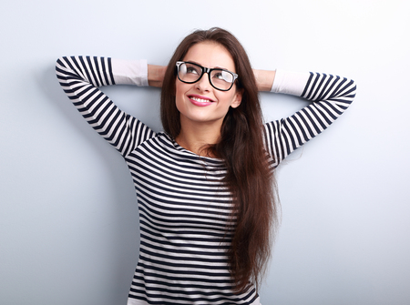 smiling people: Beautiful relaxing woman in glasses looking up with thinking look on blue background with empty copy space