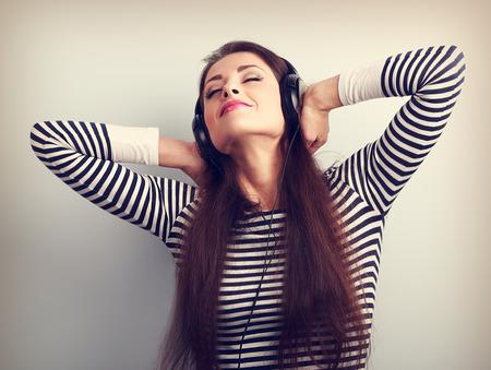 audifonos: Mujer hermosa joven que escucha la música de los auriculares con los ojos cerrados disfrutando. Retrato en tonos vintage