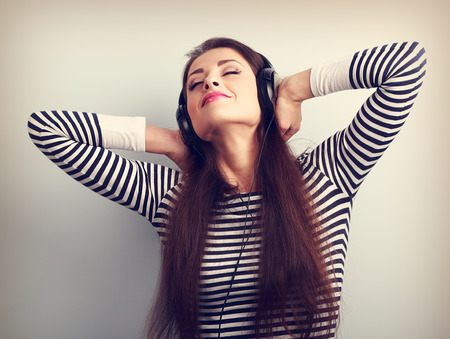 Young beautiful woman listening the music from headphones with closed enjoying eyes. Vintage toned portrait Stock Photo