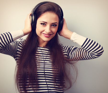one woman: Happy young woman in headphones listening the music. Vintage closeup portrait Stock Photo