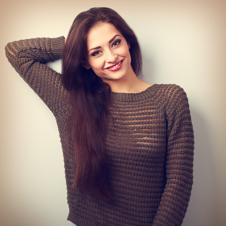 Happy young positive emotion brunette woman smiling in warm sweater. Vintage closeup toned portrait Stock Photo