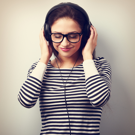 portrait: Happy smiling young woman listening the music from headphones. Vintage closeup portrait Stock Photo