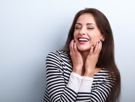 Happy loudly laughing woman holding hands the face on blue background