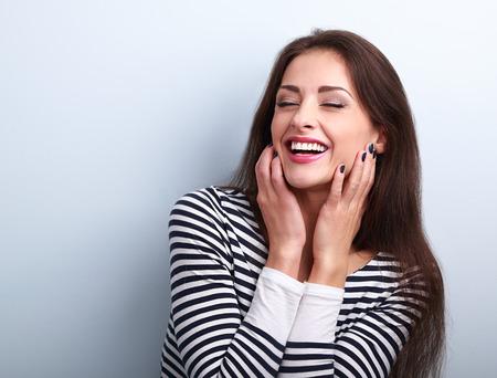 Bonne femme en riant bruyamment tenant par la main le visage sur fond bleu Banque d'images