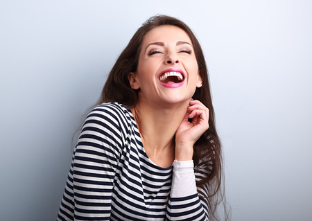 Laughing young casual woman with wide open mouth and closed eyes on blue background Foto de archivo
