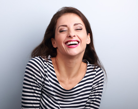 enjoyment: Happy natural toothy laughing casual woman with wide open mouth and closed eyes on blue background