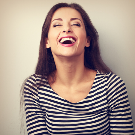 mouth closed: Happy natural laughing young casual woman with wide open mouth and closed eyes. Vintage closeup portrait