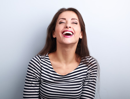 hands on mouth: Happy natural laughing young casual woman with wide open mouth and closed eyes on blue background
