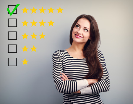 five stars: The best rating, evaluation. Business confident happy woman voting to five yellow star to increase ranking. On grey background