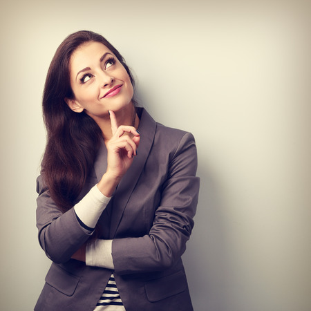 mujer trabajadora: Pensamiento mujer de negocios joven hermosa y mirando hacia arriba con el dedo debajo de la cara. Virada retrato de cerca Foto de archivo
