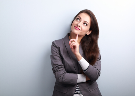 Beautiful young business woman thinking and looking up on blue background
