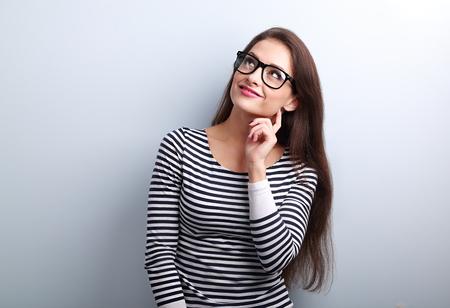 mujer pensando: Mujer bonita pensamiento ocasional en gafas mirando hacia arriba sobre fondo azul con copia espacio vacío