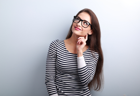 woman  glasses: Pretty casual thinking woman in glasses looking up on blue background with empty copy space
