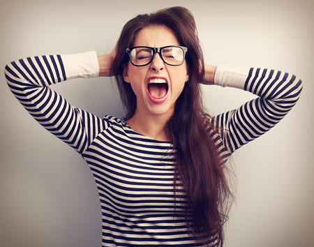 stressed business woman: Angry young business woman in glasses strong screaming with wild open mouth and holding head the hands. Toned closeup portrait