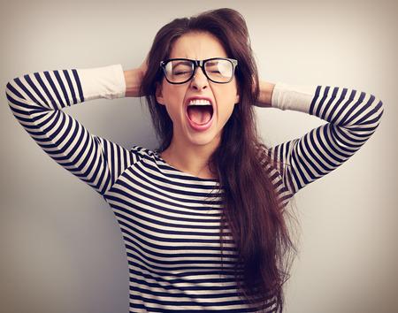 personas enojadas: Mujer enojada de negocios joven en vidrios fuertes gritando con salvaje boca abierta y la celebraci�n de la cabeza las manos. Virada retrato de cerca Foto de archivo