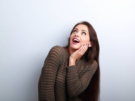 woman open mouth: Excited surprising young woman with open mouth looking up on blue background