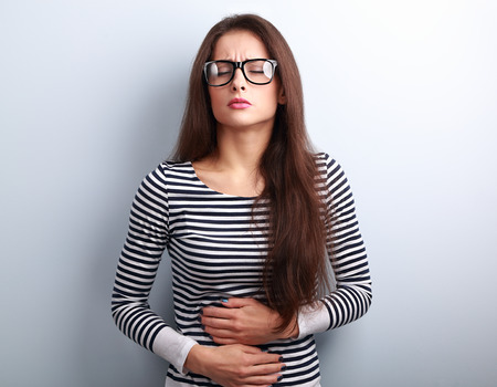 abdominal: Beautiful stressed business woman in eyeglasses suffering from pain in stomach on blue background