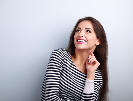 Happy emotional woman thinking and looking up with toothy smiling on blue background Stock Photo - 49157072