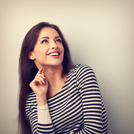Happy emotional woman thinking and looking up with toothy smiling. Vintage portrait