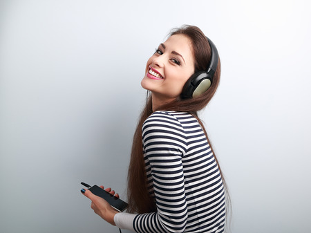 smile face: Laughing beautiful woman holding player and listening music in headphones on blue background