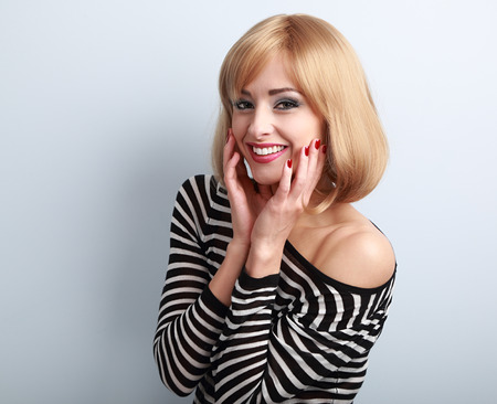 blonde woman: Laughing beautiful blond woman with short hairstyle in fashion blouse on blue background