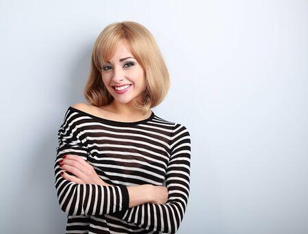 cabello rubio: mujer rubia feliz ocasional hermosa con los brazos cruzados mirando con sonrisa en el fondo azul Foto de archivo