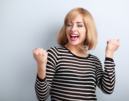 jubilate: Happy excited winner with opened mouth. Happy blond young satisfacted woman showing the gesture by fists on blue background