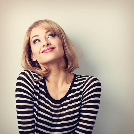 personas mirando: Diversión hermosa rubia pensamiento mujer joven en el suéter mirando hacia arriba. Retrato en tonos vintage