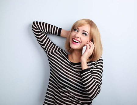 emotion: Happy emotional young blond woman talking on mobile phone and looking up on blue background