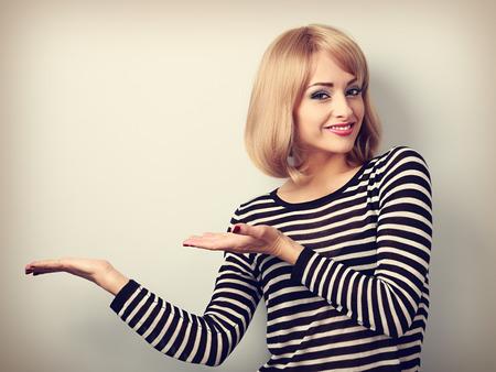 productos de belleza: Maquillaje Hermosa mujer rubia que sostiene y que presenta algo en la mano con sonrisa feliz. Retrato virada