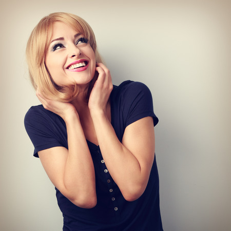 Happy laughing young woman with blond hair style looking up. Toned portrait