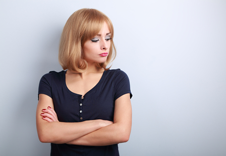 resentful: Resentful unhappy casual woman with short blond hair looking down on blue background